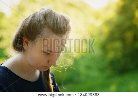 pretty teen girl looking down and thining about something in park, sunset light