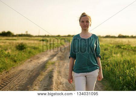 teen girl walking on dirt rural road between fields, summer time
