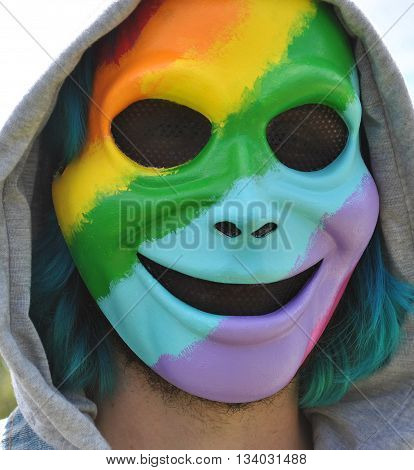 Gay pride rainbow face displayed outdoors at an outdoor pride event.