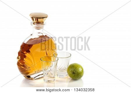 Bottle and shot glasses of tequila with lime on a white background