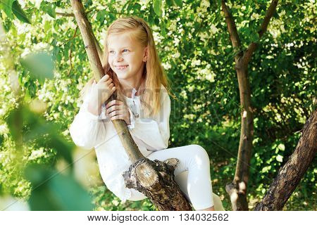 Little girl sitting on a tree and chatting her legs. Childhood
