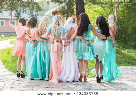 the bride with her friends. back of the beautiful bride with her friends