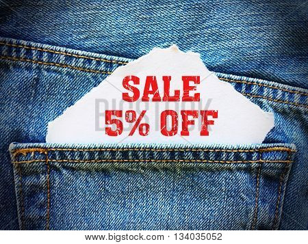 5% off on white paper in the pocket of blue denim jeans