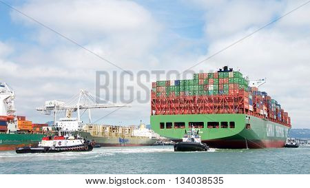 Oakland CA - June 09 2016: Multilple tugboats assist Cargo Ship CSCL WINTER maneuver into the Port of Oakland the fifth busiest port in the United States.