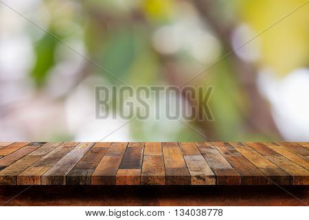 Empty wooden table with bokeh abstract green background. For display or montage your products.
