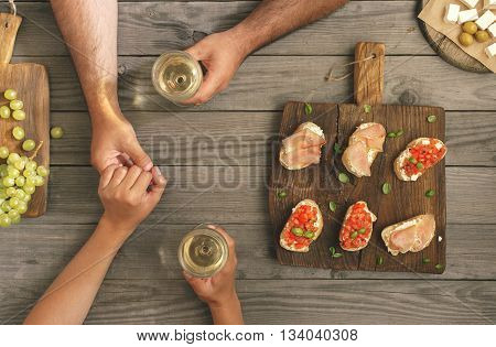 Man tenderly holds his girlfriend's hand. Couple drinking wine with snacks for wine top view