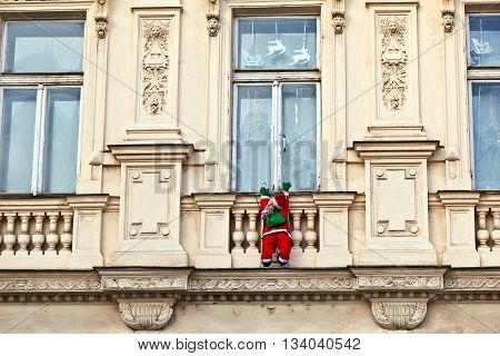 Santa claus is climbing up a historic facade