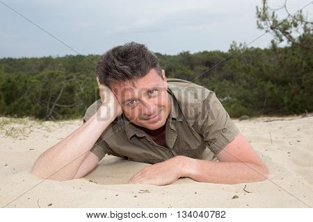 Man On Beach Lying In Sand Looking To Side