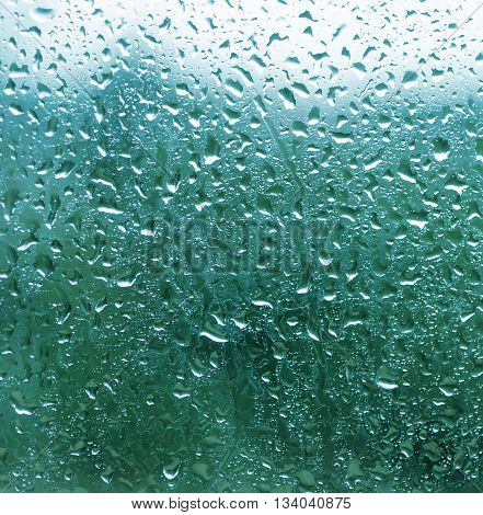 Rainy wet cold blue sky eco seasonal natural blurred background with water drops