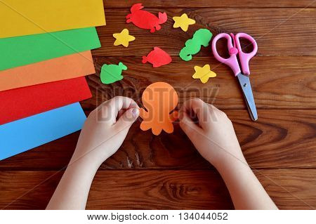 Cut out of colored paper marine animals - octopus, fish, starfish, seahorse, crab. Little child holds a octopus crafts in hands. Kids diy, sheets of colored paper, scissors on wooden background