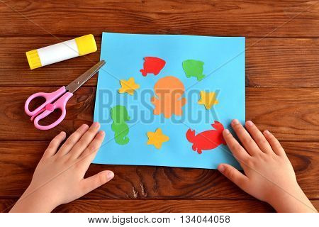 Card with bright paper sea animals and fish, glue, scissors on a brown wooden background. Summer crafts idea project for kids and babies. Child put his hands on a table. Close-up