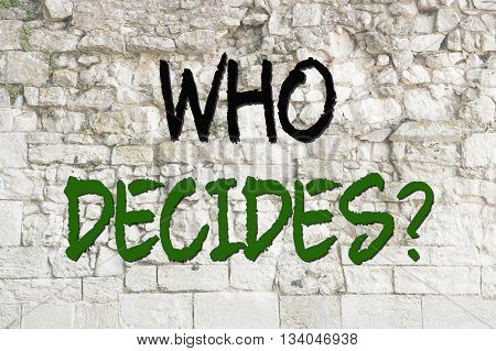 Text who decides concept on a old wall as background