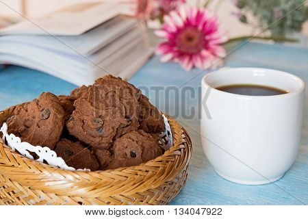 chocolate chip cookies with cup of coffe on blue table background