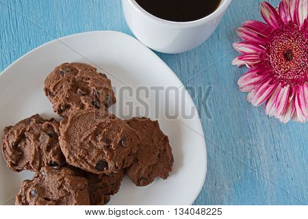 chocolate chip cookies on white plate wih cup of coffe on blue background