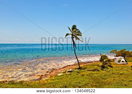 beautiful scenic beaches and clear water in the Keys with tent and people in the ocean