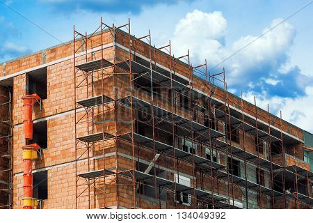 Scaffolding around the unrendered and unplastered building at construction site of new residential apartments district.