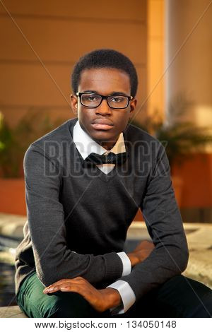 An African American teen male stares confidently into the lens of the camera as he poses for a high school senior portrait. He is wearing a sweater and bowtie.