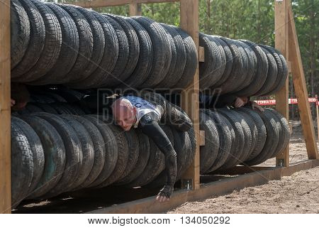 Tyumen Russia - June 11 2016: Race of Heroes project on the ground of the highest military and engineering school. Athlete moves between old tires. Human birth stage