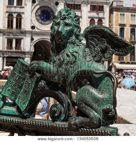 Bronze Winged Lion Statue and Torre dell'Orologio building in background in St. Mark's Square Venice Italy