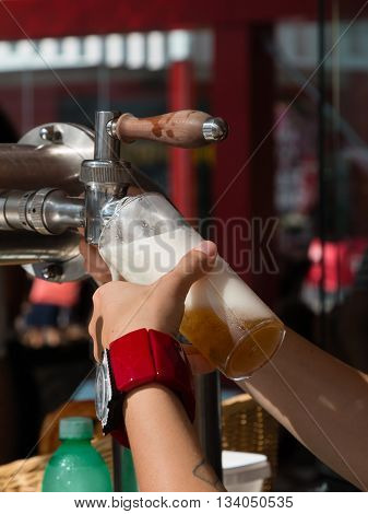 Waitress Hand Pouring a Pint of Beer from the Tap