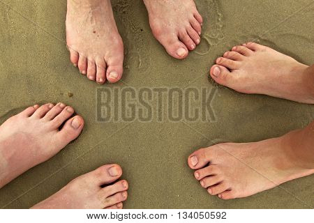 feet of family standing together at beach