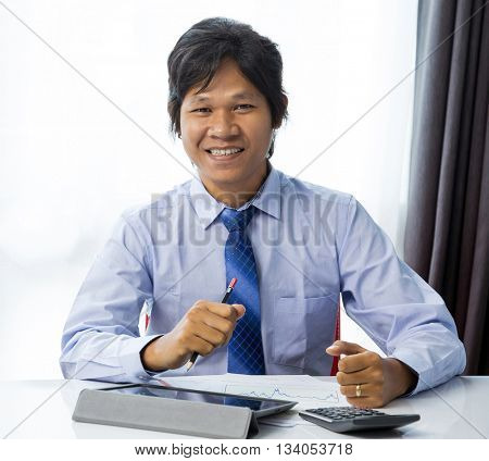Happy businessman working with tablet computer