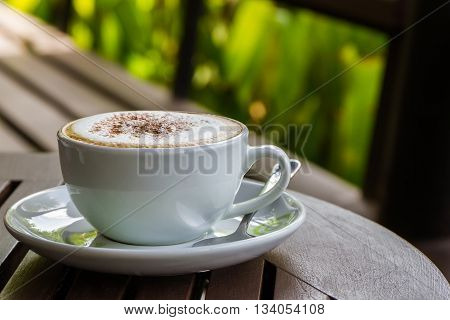 Cappuccino or latte coffee on wooden table in the cafe.