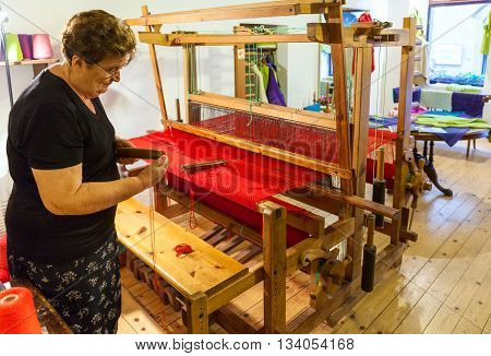 Montepulciano Italy - August 26 2013: Woman weaver working at the loom and weaves the red carpet in weaving workshop. The woman inserts the thread into the hook.