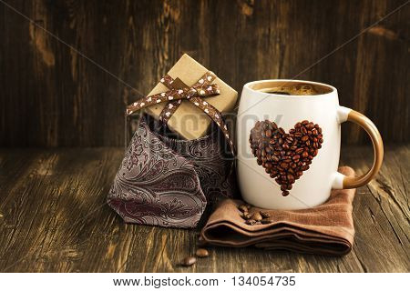 Happy Fathers Day Card. Mug of coffee, gift box and tie over wooden table. Vintage style. Toned image. Selective focus