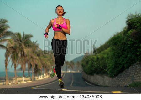 Runner woman running on beach road in beautiful nature. Female sport fitness model jogging training for marathon during outdoor workout.