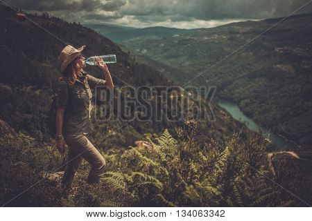 Woman hiker with backpack drinking fresh water from a bottle on a top of mountain.