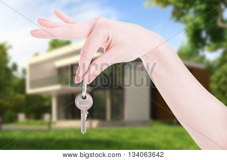 Female Hand Hanging House Key As Real Estate Concept