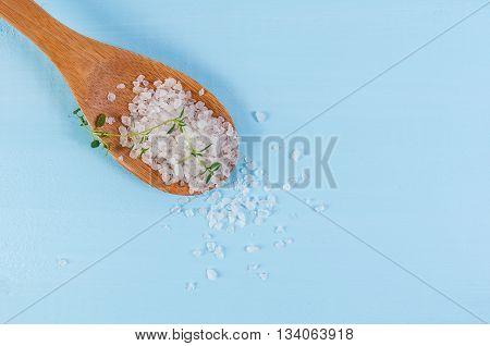 Sea salt over wooden background, selective focus, close up