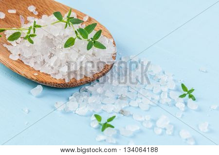 Sea salt over wooden background, selective focus, close up
