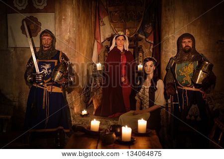Medieval queen with her courtier and knights on guard in ancient castle interior.