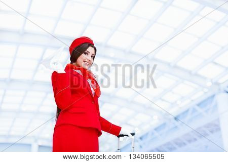 Young stewardess with a plane at airport