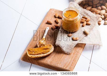 Homemade almond butter in a glass jar and sandwich smeared with a ceramic spoon.