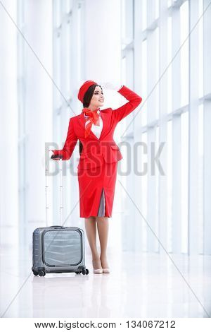 Smiling stewardess with luggage at airport