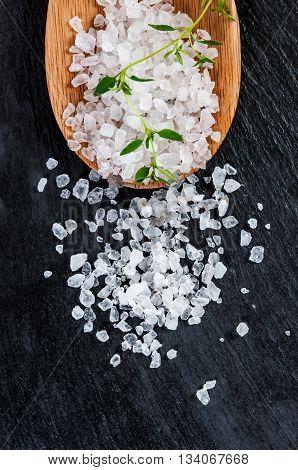 Sea salt over black slate background, selective focus, close up