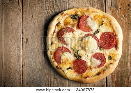 Pizza Margherita with tomatoes and mozzarella cheese on a wooden surface