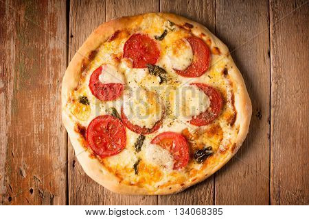Pizza Margherita with tomatoes and mozzarella cheese on a wooden surface (horizontally oriented photo)