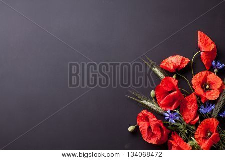 Heads of red poppies rye and cornflowers in the corner of black background flat lay