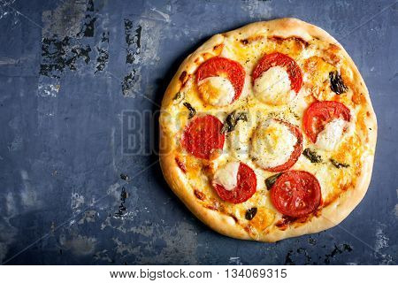 Pizza Margherita with tomatoes and mozzarella cheese on a blue old effect surface