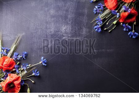 Red poppies with blue cornflowers and rye on the corners of old blackboard with scratches