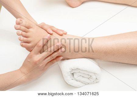 Foot massage therapist's hands massaging female foot