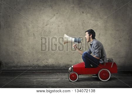 Young man shouting from a toy car