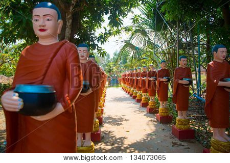 Sculptures Of Priests In Red Clothes, In The Hands Of The Bowl.siemreap,cambodia.