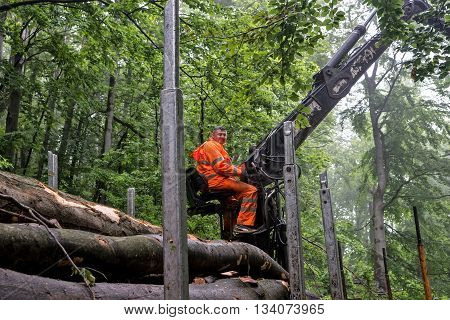 Brezovica Serbia - May 12 2016: Loading wooden logs on mountain road on truck with crane