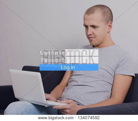 Young Handsome Man Sitting On Sofa With Computer And Registering Account In Social Network