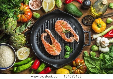 Dinner cooking ingredints. Raw uncooked salmon fish with vegetables, rice, herbs, spices and oil in iron grilling pan over rustic wooden background, top view